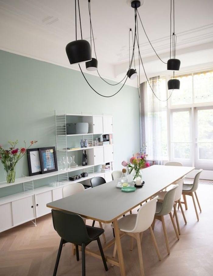 modele de salle à manger vert celadon, parquet clair, table en bois avec plateau gris, chaises scandinaves blanches et une chaise noire, suspensions noires, meuble blanc avec plusieurs étagères