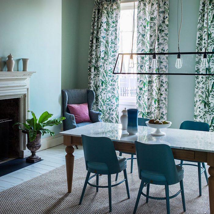 modele de salle à manger vert pastel, teinte céladon, table en bois avec plateau en marbre, chaises bleu canard, tapis gris, cheminée rustique, linge de lit blanc et vert, parquet clair blanchi, lustre en ampoules électriques