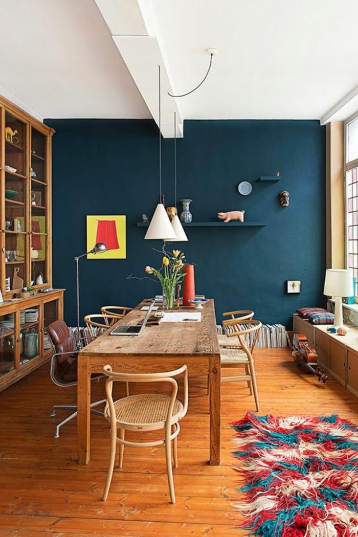 deco salon bleu canard ouvert sur la salle à manger avec grande table en bois et des étagères au mur avec des objets déco