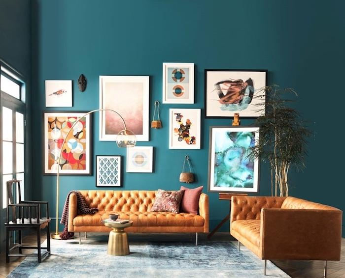 salon moderne bleu petrole peinture, deco murale de cadres colorés originaux, canapé en cuir orange, tapis bleu et blanc, table basse couleur or