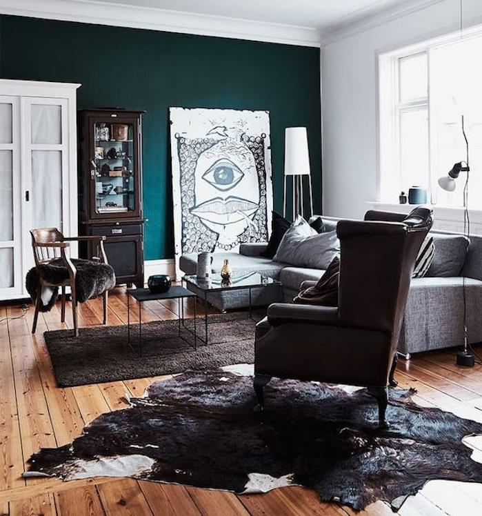 modele de salon bleu petrole artistique, parquet marron, canapé, fauteuil et tapis gris, peau animal, mur de fond, teinte verte, panneau decoratif noir et blanc insolite, décor vintage artistique