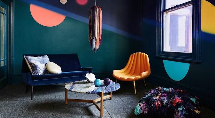 exemple de salon bleu petrole, peinture bleu pétrole, canapé bleu marine, fauteuil orange, revêtement sol gris, table basse avec plateau en marbre, pouf et suspension colorés