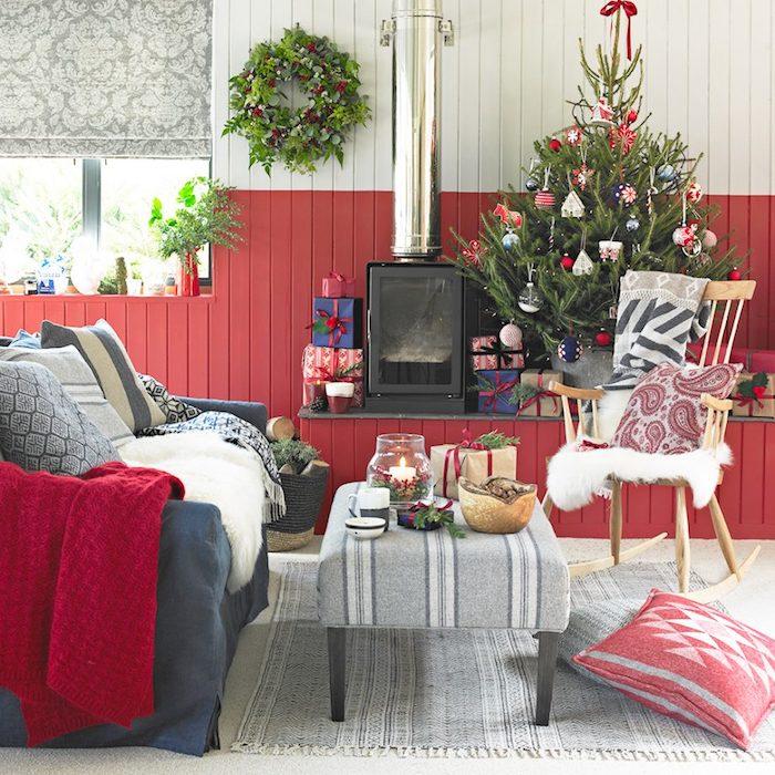 salon cocooning en rouge et blanc, avec canapé gris et coussins gris, chaise à bascule en bois vintage, deco sapin de noel en ornements blanc, rouge et bleu, couronne de noel, cheminée noire