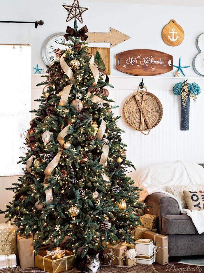 salon cocooning décoré de boules de noel argent et doré, pommes de pin, guirlande lumineuse et guirlande de rubans dorés, étoile sur le pic, paquets cadeaux dorés, canapé gris, deco murale style bord de mer