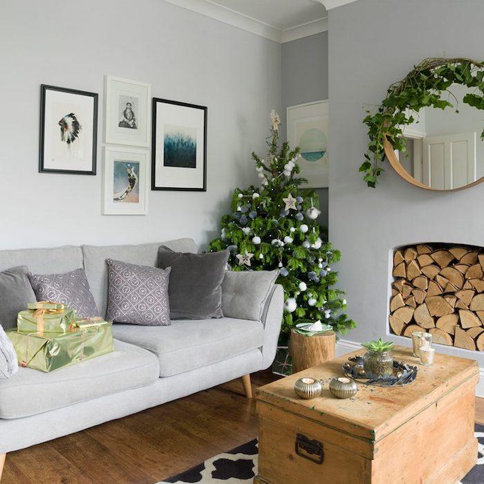 sapin de noel décoré d ornements blancs et gris, cheminée blanche, canapé gris, table basse en coffre bois vintage, tapis noir et blanc