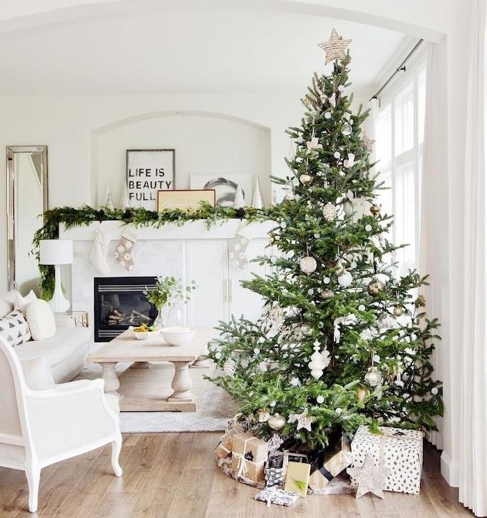 salon scandinave en blanc avec sapin de noel decoration en ornements blanches, canapé, chaise blancs, cheminée décoré d une guirlande de pin