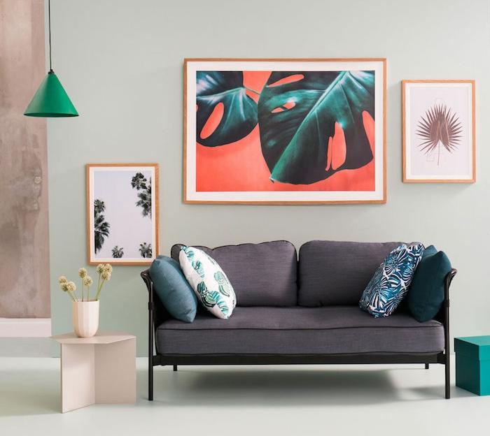 modele de salon vert d eau, nuance vert gris, canapé gris, coussins à motif de plantes exotiques, table d appoint en bois, sol vert pistache, suspension vert emeraude, deco murale de cadres motif palmier
