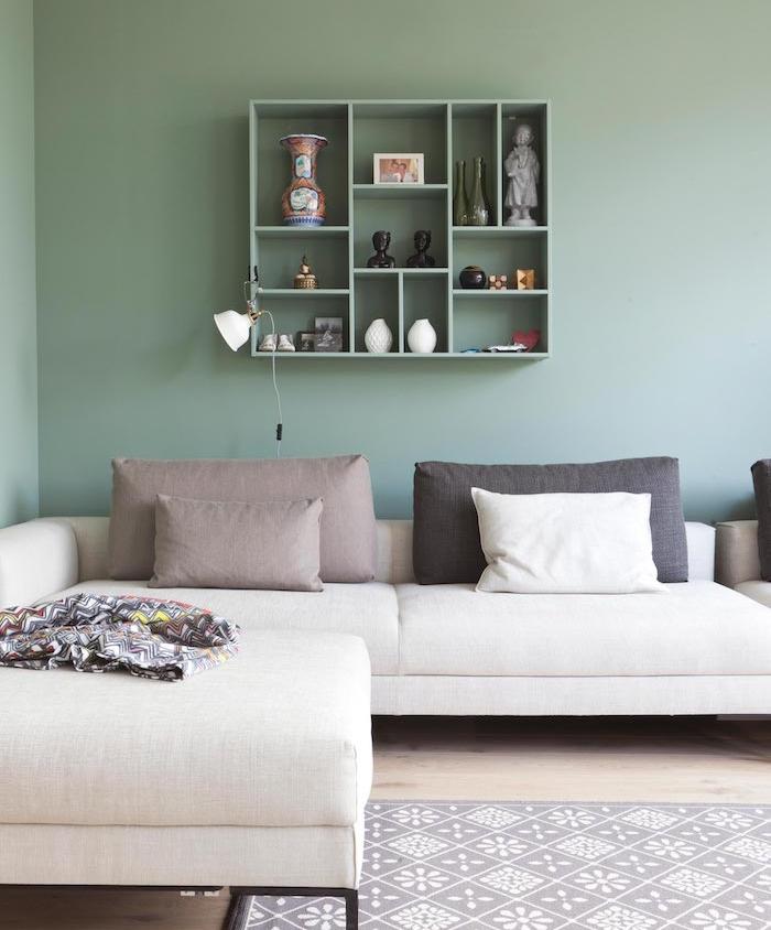 amenagement de salon couleur vert celadon, canapé d angle blanc cassé, coussins gris, tapis gris et blanc, parquet clair et étagère ouverte verte, rangement accessoires deco bouddhistes