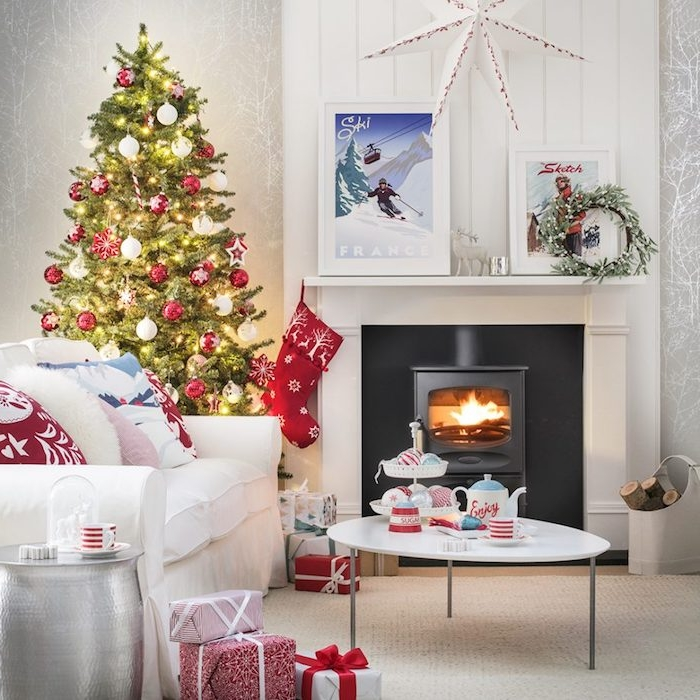 sapin décoré en rouge et blanc et guirlande lumineuse dans un salon cocooning avec cheminée blanche, canapé et table basse blanc, coussins e paquets cadeaux rouge et blanc