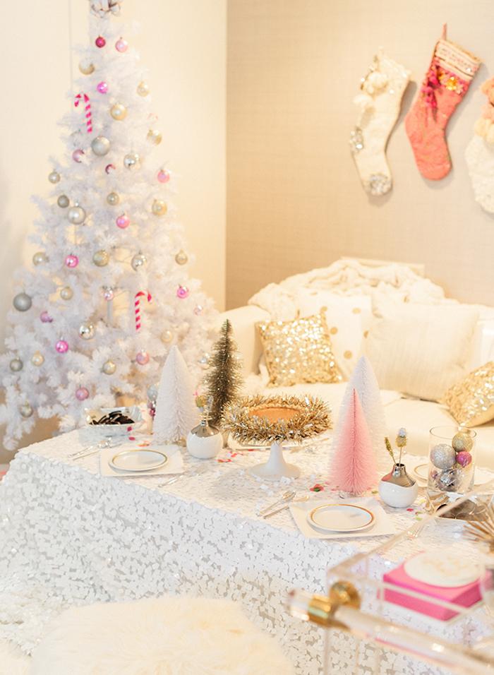 modele de sapin de noel blanc, décoré de boules de noel rose, or et argent, canapé et nappe table blanche, chaussettes suspendues au mur et détails déco dorés