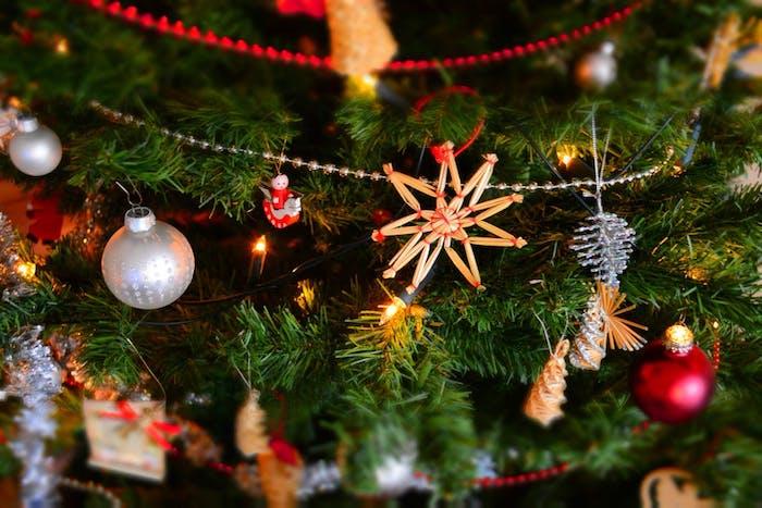 arbre de noel vert décoré d ornements noel, petits sapins dorés et argentées, boules de noel, etoiles diy, guirlandes de perles