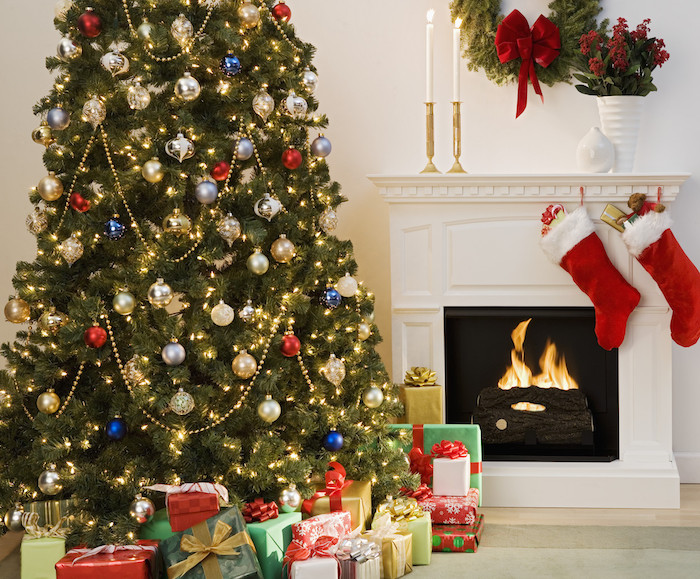 décoration sapin de noel, paré de boules de moel or, argent, bleues et rouges, guirlande lumineuse et guirlande de perles dorées, cheminée blanche, paquets cadeaux colorés