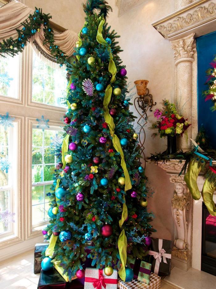 comment décorer un sapin de noel de boules de noel bleues, violettes, jaunes et vertes et guirlande de rubans verts, cheminée romaine et pied d epaquet cadeaux