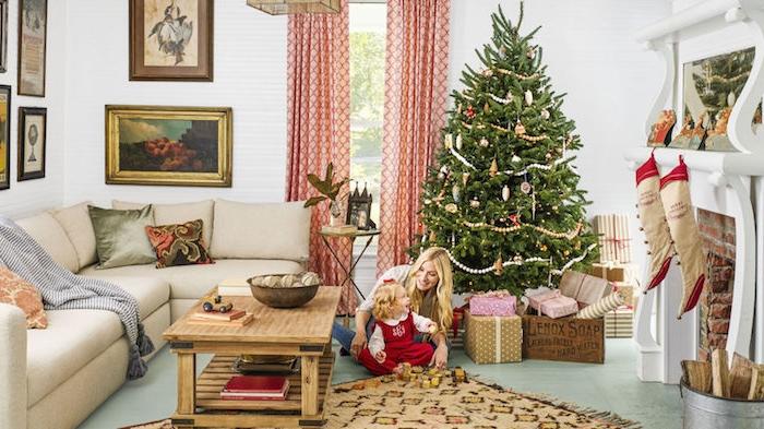 sapin de noel naturel, décoré de guirlande de perles or et argent, petits ornements, cheminée blanche, canapé gris et table basse en bois