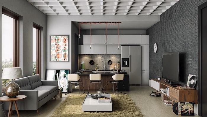 exemple de separation cuisine salon avec bar en bois, façade cuisine grise, suspensions insutrielles, mur en briques gris, canapé gris perle et tapis beige, table basse minomaliste