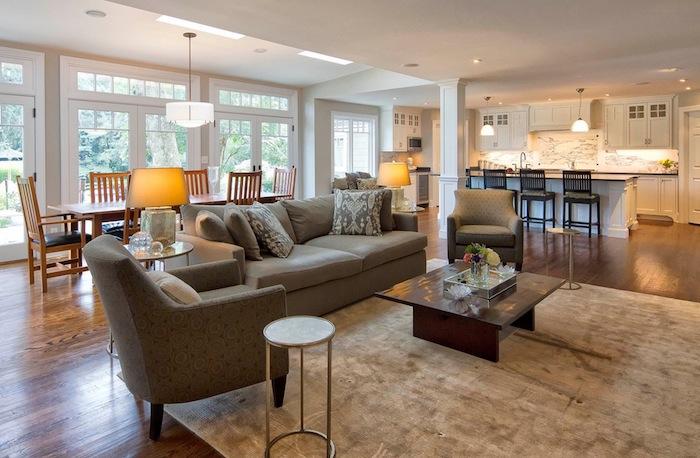 separation cuisine salon par un bar blanc entouré de chaises en bois, facade meuble cuisine blanche et crédence effet marbre, canapé gris, table en bois et verre, tapis gris, salle à manger bois