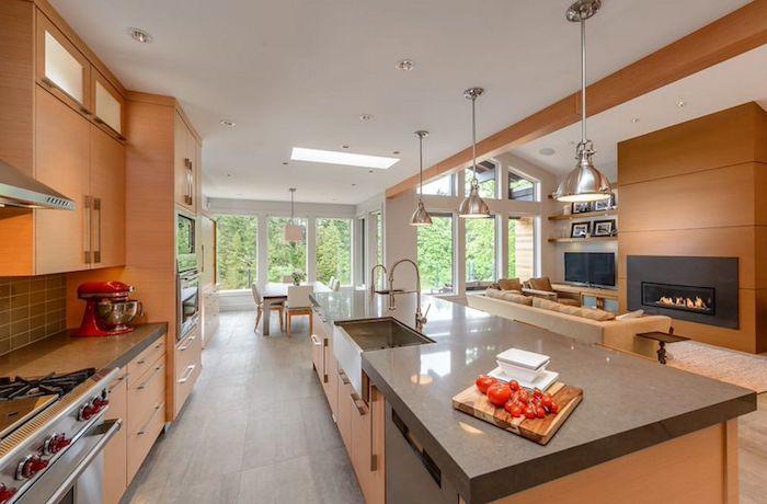 exemple de separation cuisine salon par un bar en bois, facade meuble cuisine bois, ouverture salon avec canapé beige et cheminée en bois romantique, suspensions industrielles