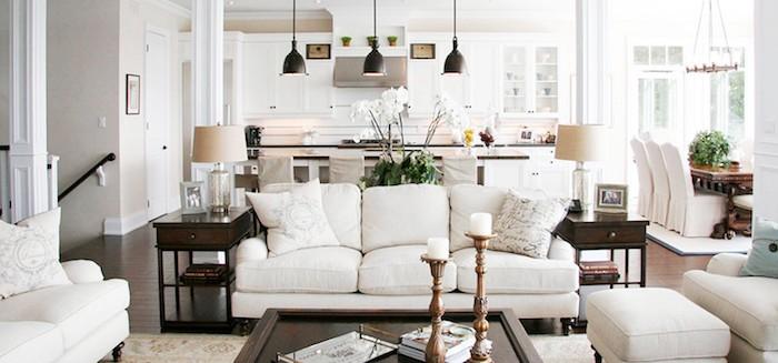 modele de cuisine ouverte blanche traditionnelle, salle à manger en table en bois massive et chaises revêtues de housses blanches, salon avec caanpés blancs, table basse en bois