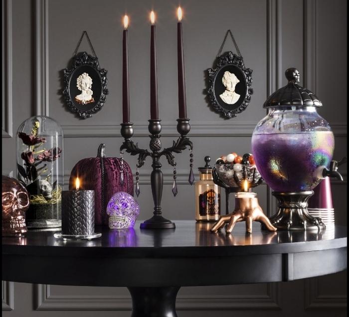 deco halloween a faire soi meme, salox aux murs gris avec portraits en cadre noir, table ronde noire avec objets décoratifs Halloween
