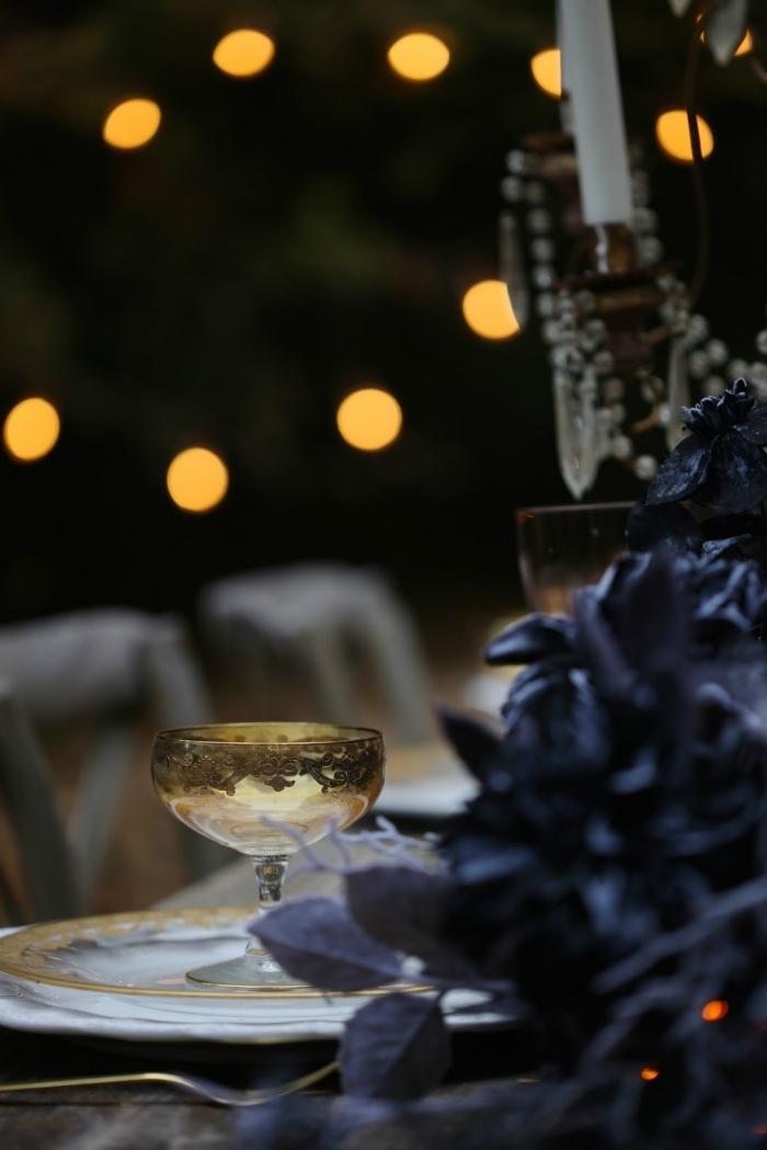 idee deco halloween de la table, guirlande lumineuse au-dessus de la table à manger décorée avec guirlande en feuilles séchées noires
