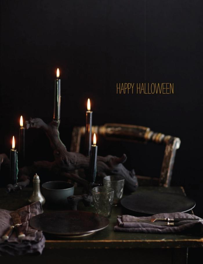 repas halloween, idée comment arranger la table Halloween, table noire avec chaise en bois vieillit et bougies noires