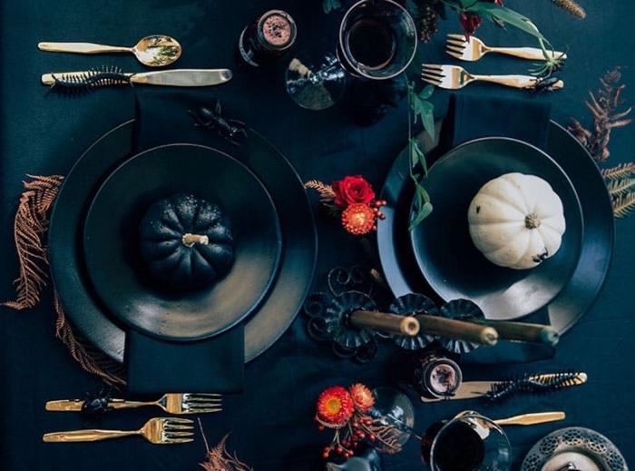 arrangement table Halloween avec nappe noire, assiettes et bougeoirs noirs pour Halloween avec petites citrouilles décoratives