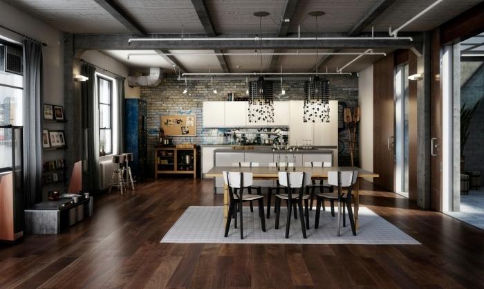 déco de studio loft, pièce aux murs briques avec plafond en poutres bois et plancher en bois stratifié foncé