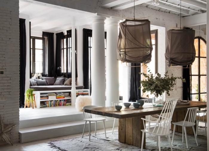aménagement de style loft, pièce aux murs briques blanches avec plancher en bois et rideaux longs noirs
