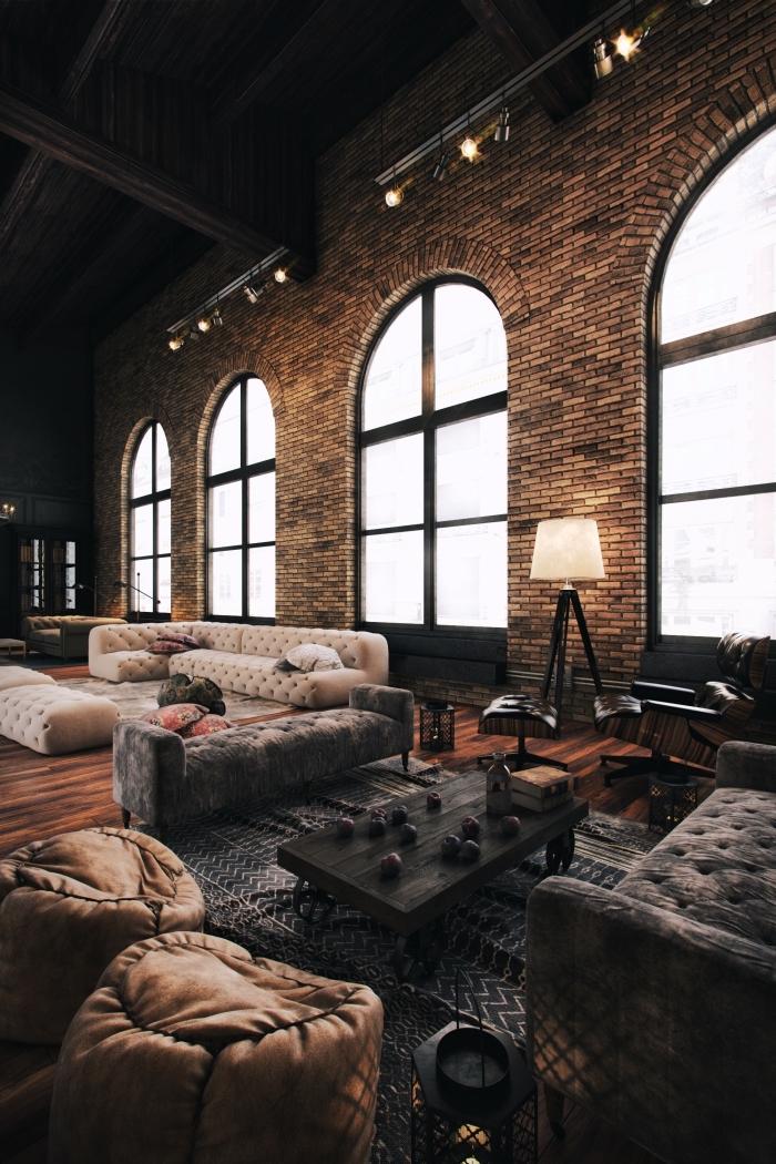 déco loft industriel, meubles en velours foncé avec table basse en noir, pouf en cuir marron et lampe sur pied jaune et noir