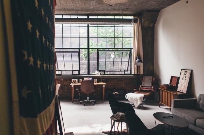chaise industrielle, pièce loft aux blancs et plafond gris, meubles en bois foncé, petite table basse en noir