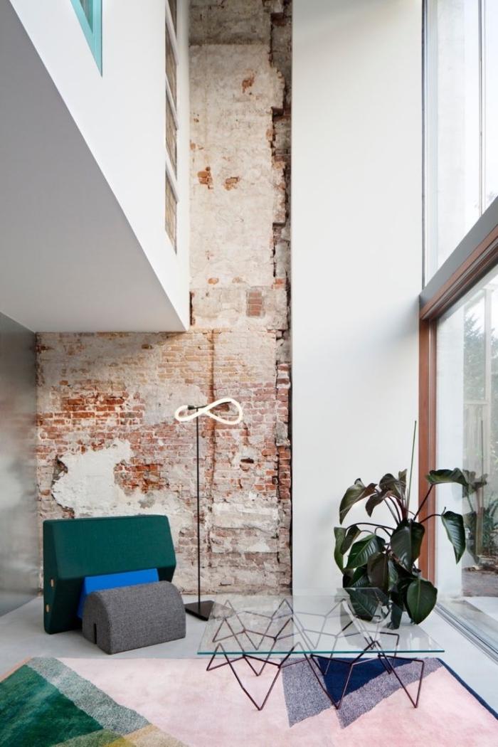 déco loft industriel aux murs briques et peinture blanche, modèle de table basse en verre, modèle de tapis multicolore