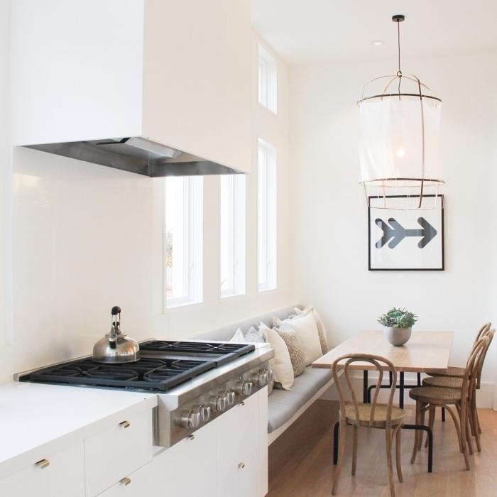 cuisine équipée, décoration intérieur aux murs blancs et plancher en bois stratifié, peinture flèche avec cadre noir
