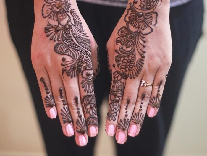 henné facile, modèle de dessin au henné noir sur les mains féminins, tatouage temporaire à design florale