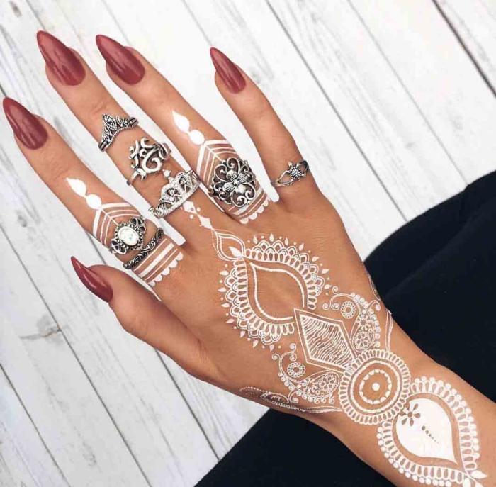 henné blanc, tatouage temporaire sur les doigts et la main, manucure aux ongles longs et vernis rouge