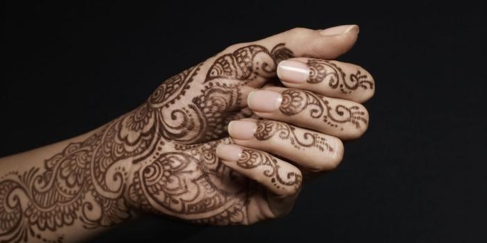 modele henné, dessin sur mains pour femme, tatouage temporaire à motifs volutes et floraux