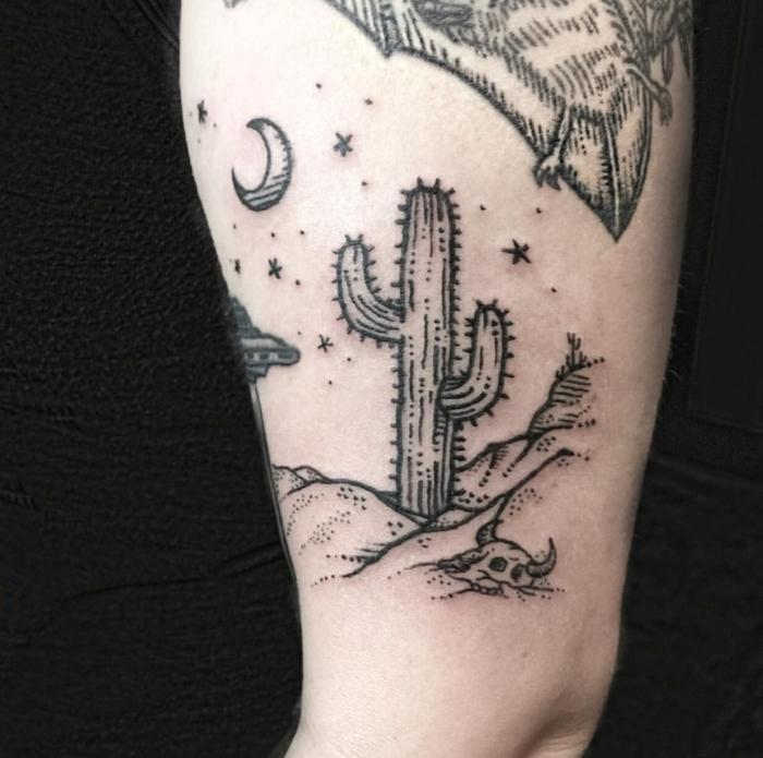 tatouage femme cuisse, paysage absurde d'un désert avec ciel étoilé, lune et grand cactus