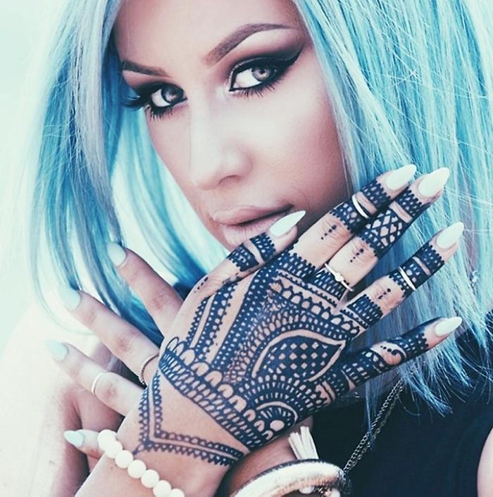 tatouage sur les mains et les doigts au henné noir, maquillage aux yeux smoky et lèvres nude avec cheveux bleus
