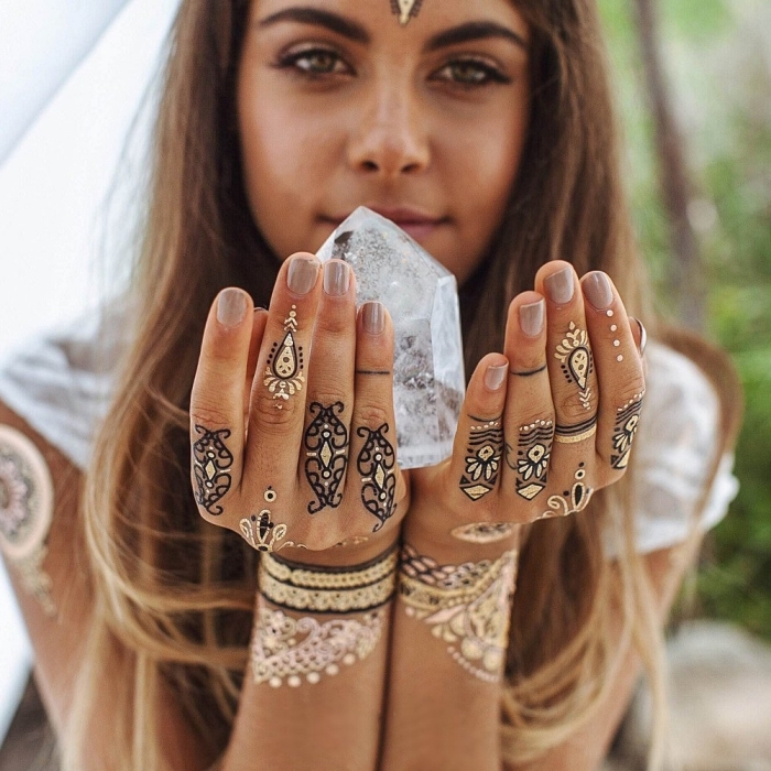 henné facile, femme aux cheveux longs en blond foncé, décoration des mains féminins au henné noir et doré