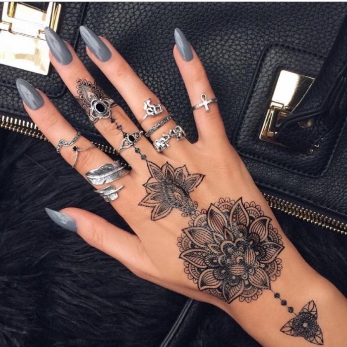 henné main simple, modèle de sac à main en cuir noir, manucure aux ongles longs et vernis gris, tattoo temporaire pour femme