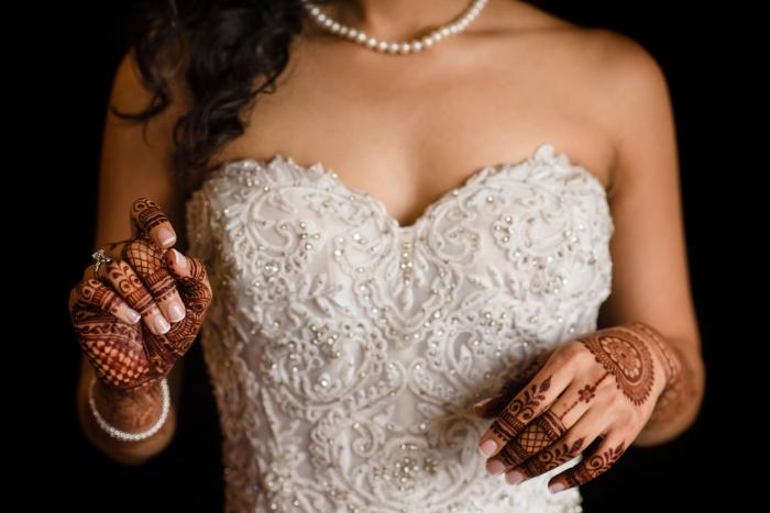 modele henné, robe de mariée blanche avec bustier en coeur et collier en perles blanches, tatouage au henné rouge sur les mains