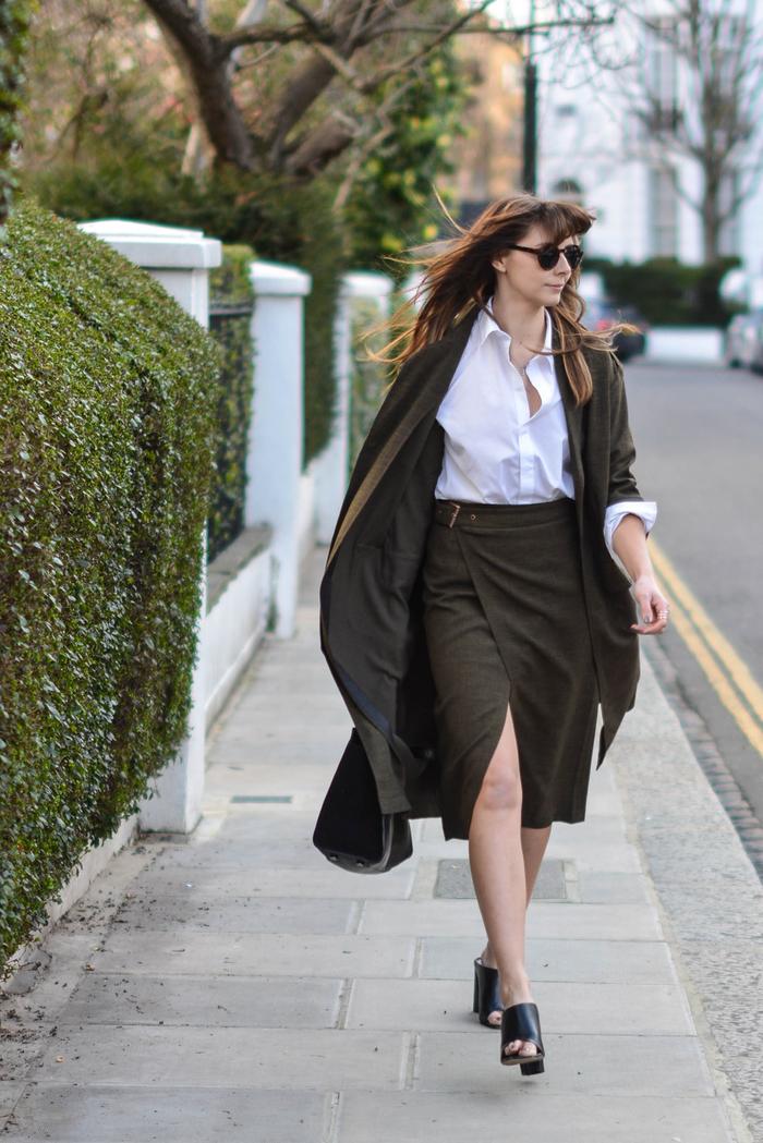 tenue élégante et sophistiquée pour aller au bureau avec manteau kaki femme fluide, jupe portefeuille de même vert olive et chemise blanche