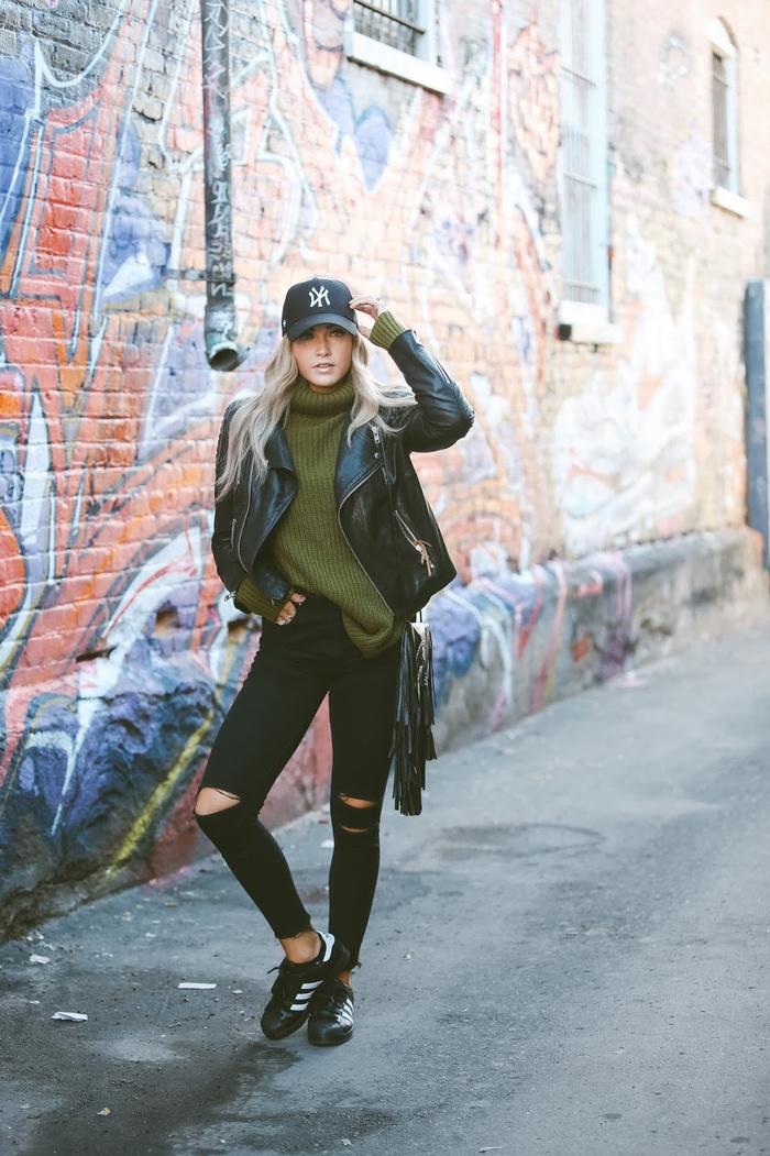 tenue swag avec un jean noir troué aux genoux, un pull vert kaki à col roulé et un blouson en cuir motarde