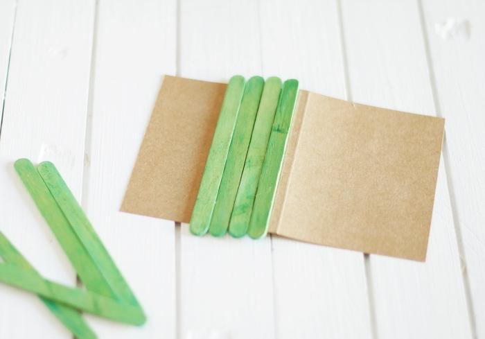 livre photo personnalisé, tutoriel pour fabriquer la couverture d'un album photo diy, papier recyclé plie en deux avec bâtons en bois peints en vert