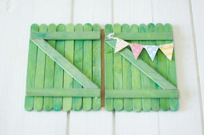 activité manuelle maternelle, petite décoration en papier en forme de guirlande multicolore sur la clôture en bois vert
