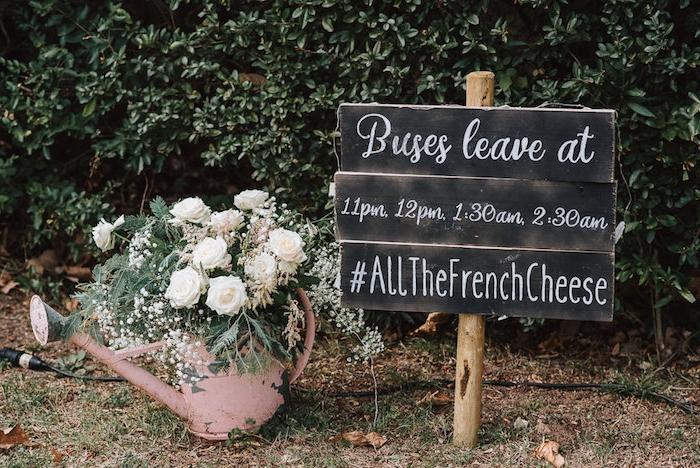 arrosoir rose rouillé rempli de bouquet de roses, planches en bois horaire des bus pour les invités, décoration champêtre