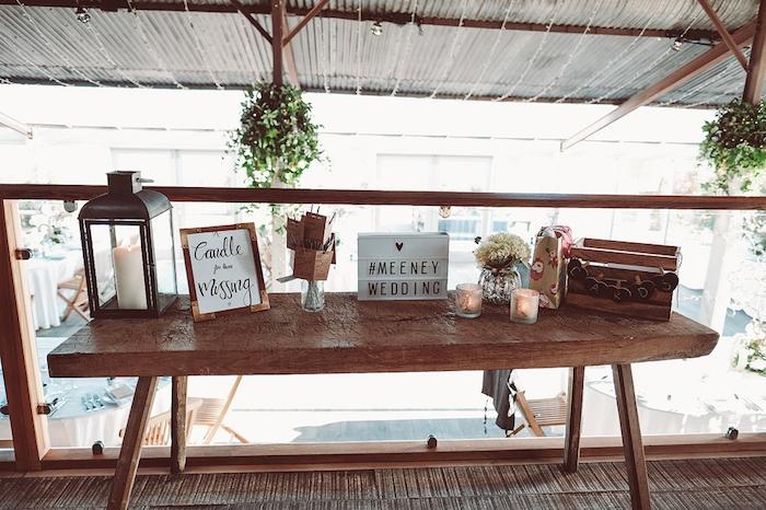 urne mariage champêtre en cagette bois, lanterne noire avec bougie, bougeoirs, pot de fleurs avec bouquet sur une table en bois rustique