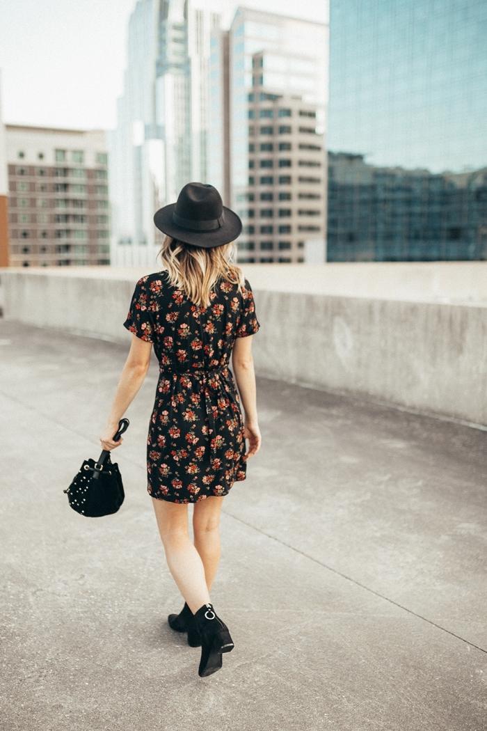 style bohème chic en capeline sac a main et bottines noirs avec robe courte noire à motifs floraux rouge et marron