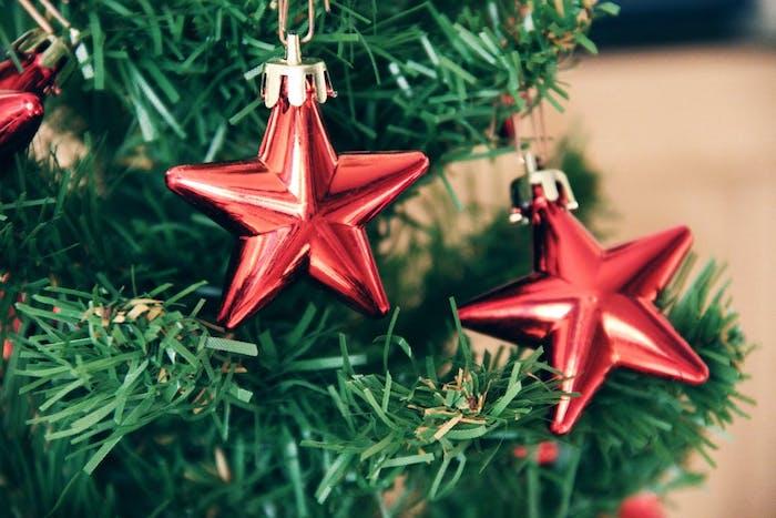 un sapin de noel artificiel décoré d étoiles rouges, fond d écran noel hd épuré