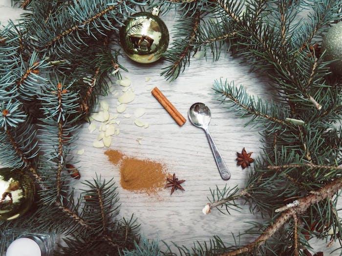 images de noël gratuites, branches de pin, cannelle, boules de noel dorées, cuillère argentée, amandes sur une surface en bois