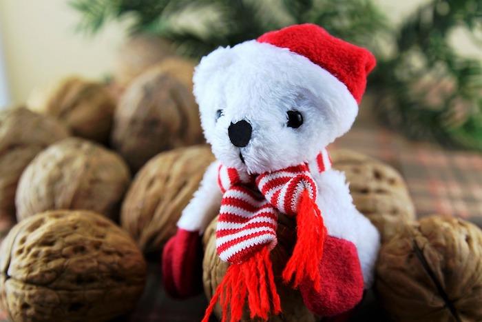 fond ecran noel en ourson peluche blanc, vêtu d un chapeau, gants et écharpe rouge et blanc noix et branches de pin vertes sur le fond